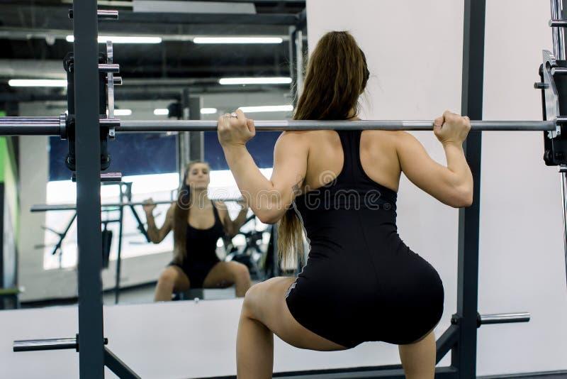 Forme physique, sport, powerlifting et concept de personnes - femme sportive s'exer?ant avec le barbell dans le gymnase photo stock