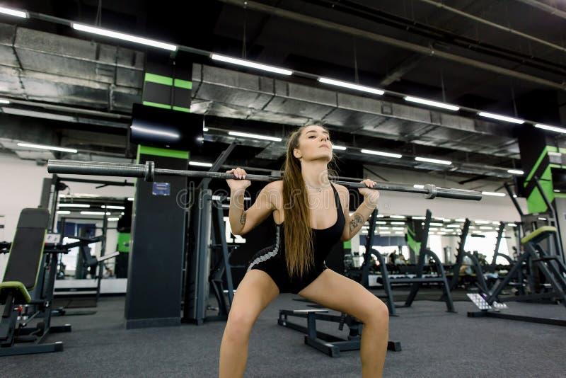 Forme physique, sport, powerlifting et concept de personnes - jolie femme sportive s'exerçant avec le barbell dans le gymnase photographie stock libre de droits