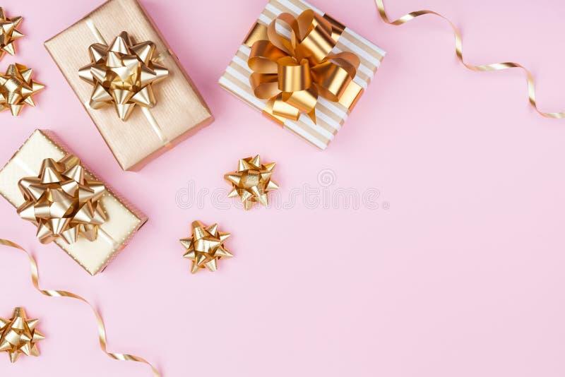 Forme presentes ou apresente caixas com curvas douradas na opinião superior do fundo pastel cor-de-rosa Configuração lisa para o  fotos de stock