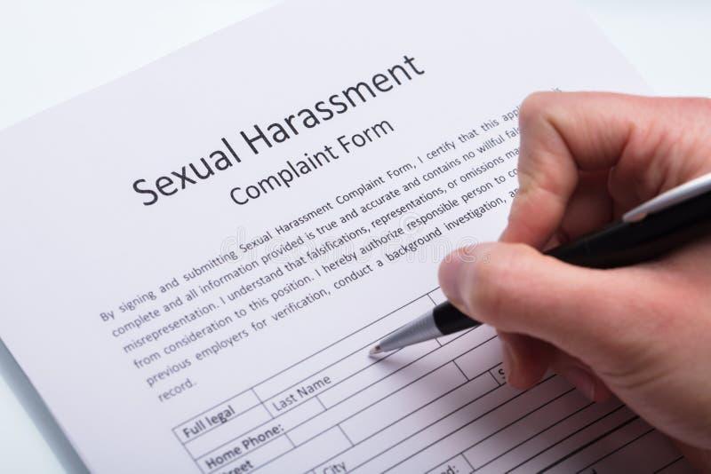 Forme remplissante de plainte de harcèlement sexuel de main humaine image stock
