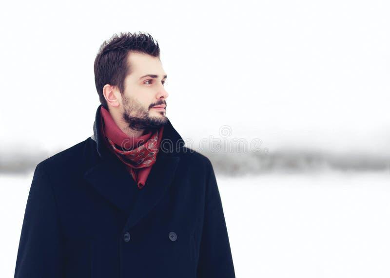 Forme a retrato el hombre barbudo elegante hermoso que lleva invierno negro de la capa sobre el fondo nevoso, mirando distancia a imagen de archivo