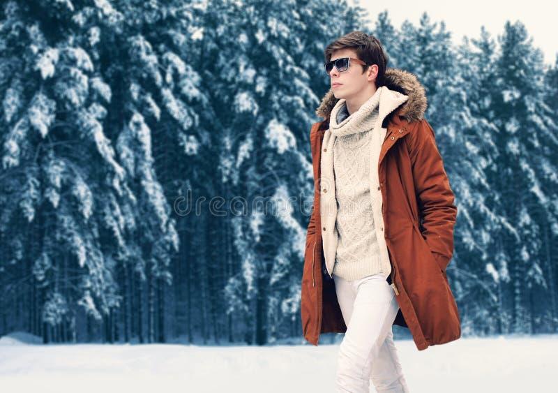 Forme a retrato la chaqueta que lleva del hombre elegante hermoso y el suéter hecho punto que caminan en bosque del invierno sobr imagenes de archivo