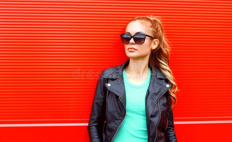 Forme a retrato la mujer hermosa en chaqueta negra de la roca de las gafas de sol sobre rojo fotos de archivo
