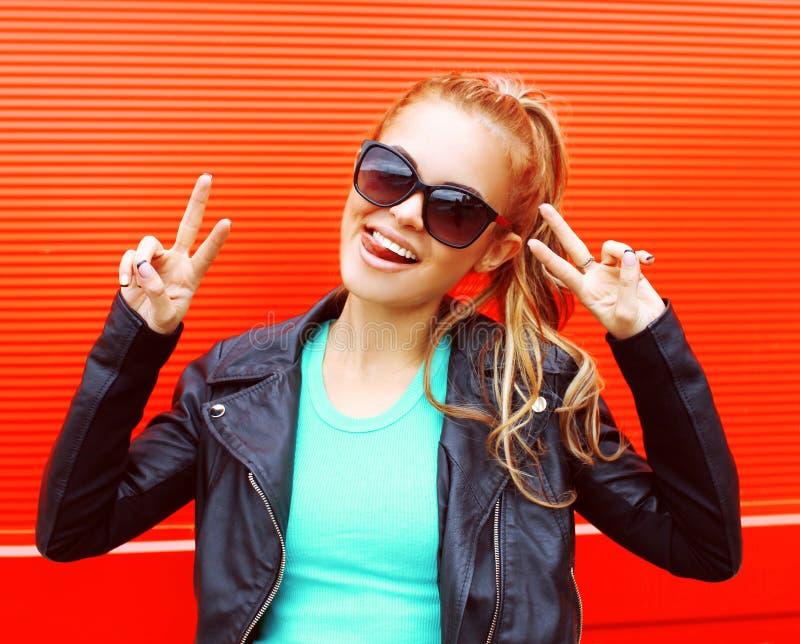 Forme a retrato la mujer sonriente joven en las gafas de sol que se divierten sobre rojo imagen de archivo