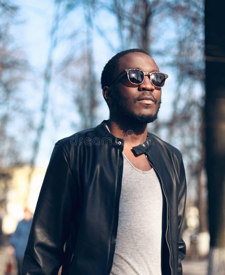 Forme a retrato las gafas de sol que llevan del hombre africano, chaqueta de cuero negra de roca en la calle foto de archivo libre de regalías