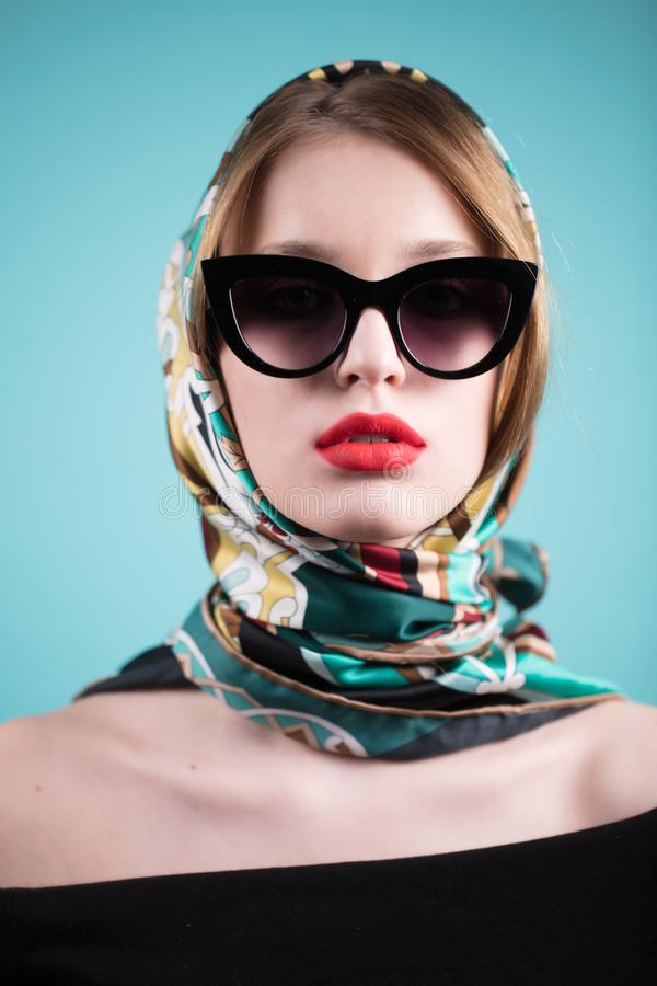Forme a retrato a mulher bonita à moda nos óculos de sol e no levantamento do lenço foto de stock