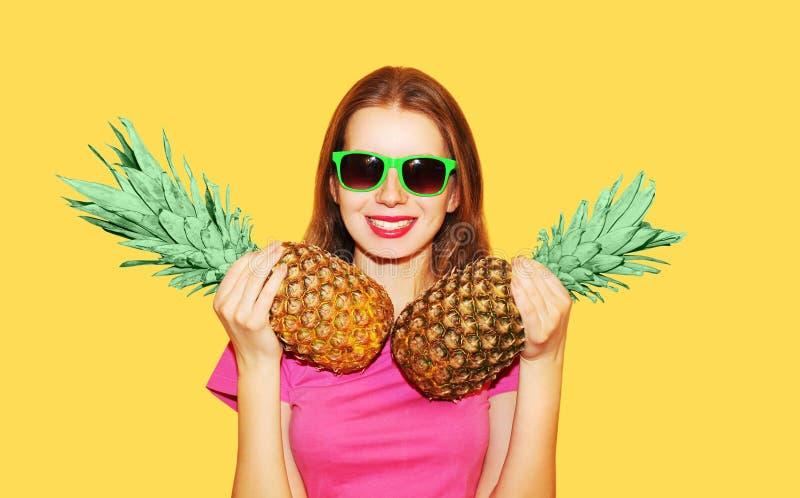 Forme a retrato a mulher e o abacaxi dois de sorriso bonitos nos óculos de sol sobre o amarelo foto de stock