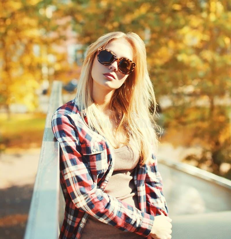 Forme a retrato vestir bonito da mulher óculos de sol e camisa quadriculado na cidade imagens de stock