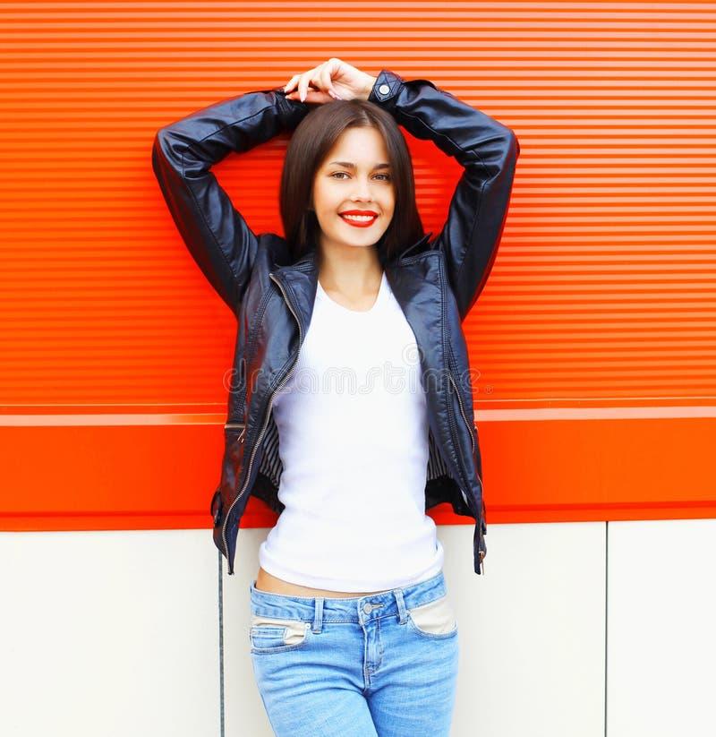 Forme a roca que lleva sonriente hermosa de la mujer joven la chaqueta negra, vaqueros en la ciudad sobre rojo colorido foto de archivo libre de regalías