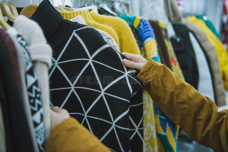 Forme a roupa na cremalheira da roupa, mão da mulher que escolhe a roupa nova, conceito da loja da forma foto de stock royalty free