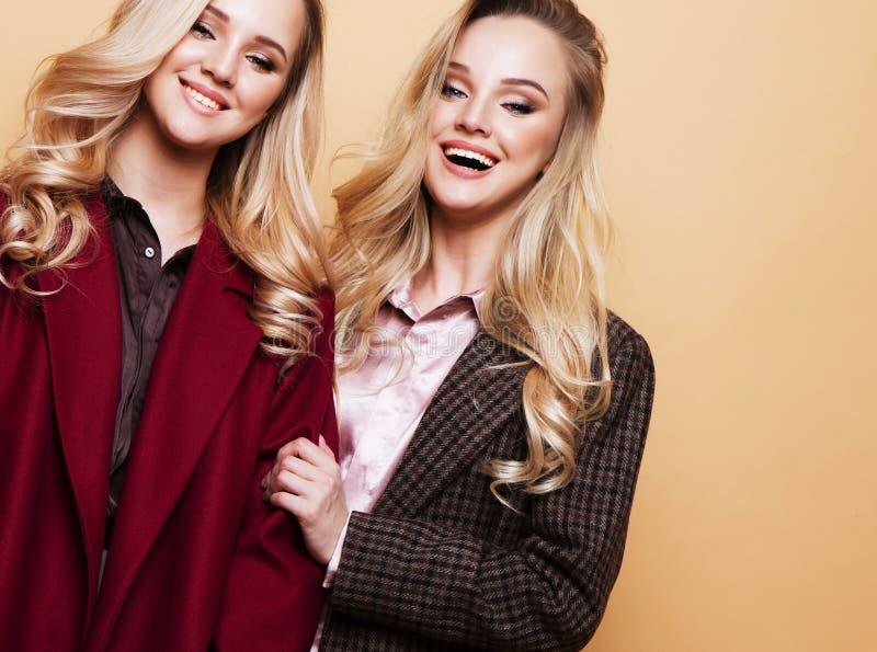 forme um retrato de duas meninas, levantamento dos melhores amigos interno no revestimento à moda vestindo do inverno do fundo be fotos de stock