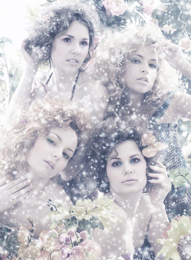 Forme um tiro de quatro mulheres bonitas nas flores imagens de stock royalty free