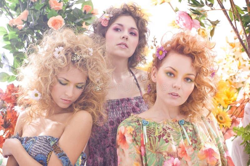 Forme um tiro de três mulheres bonitas nas flores foto de stock