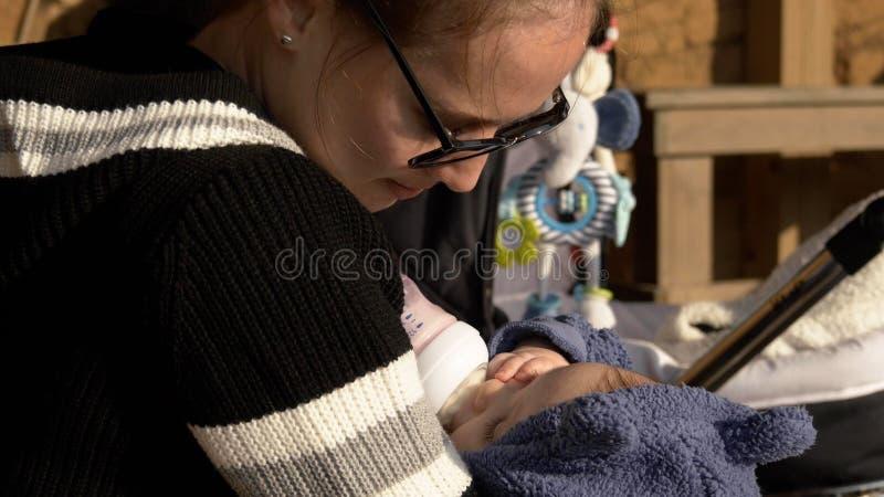 Formel im Freien, die, kleines lustiges Baby isst von der Flasche einzieht lizenzfreie stockfotos
