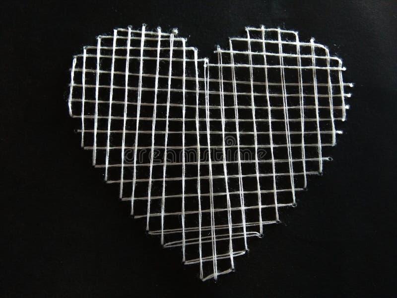 Formen av hjärtan som göras av tråden på svartpapper fotografering för bildbyråer