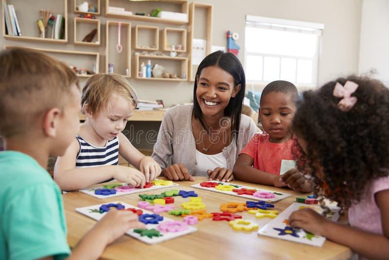 Former för lärareAnd Pupils Using blomma i den Montessori skolan royaltyfri foto