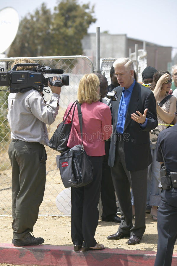 Former Governor Gray Davis being interviewed by newscaster and cameraman, CSU- Dominguez Hills, Los Angeles, CA stock image