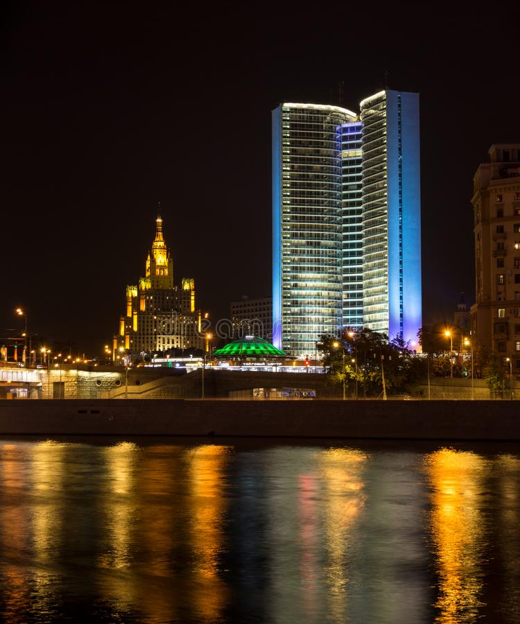 Former House of the Council for Mutual Economic Assistance Comecon with famouse Stalin skyscaper on the background in Moscow. At night. Colorful illumination royalty free stock photos
