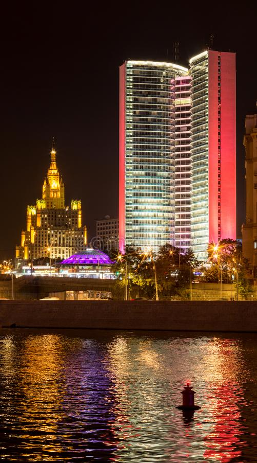 Former House of the Council for Mutual Economic Assistance Comecon with famouse Stalin skyscaper. On the background in Moscow at night. Colorful illumination stock photo