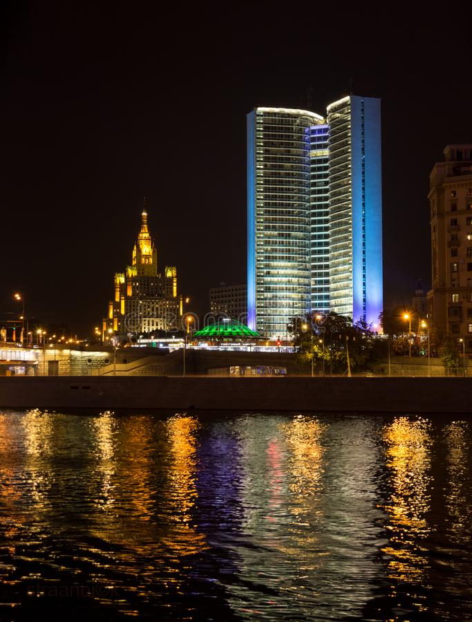 Former House of the Council for Mutual Economic Assistance Comecon with famouse Stalin skyscaper on the background in Moscow at. Night. Colorful illumination royalty free stock photo