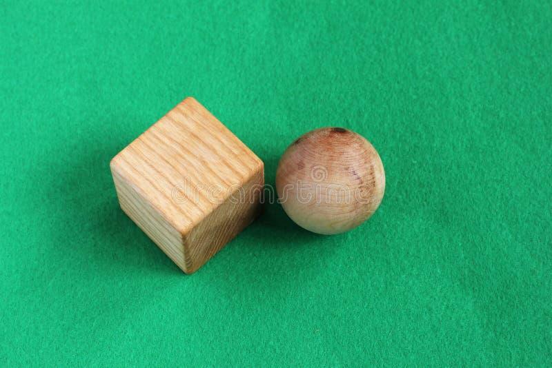 Formes géométriques en bois - boule et cube, jouets d'eco d'enfants, gree photographie stock libre de droits