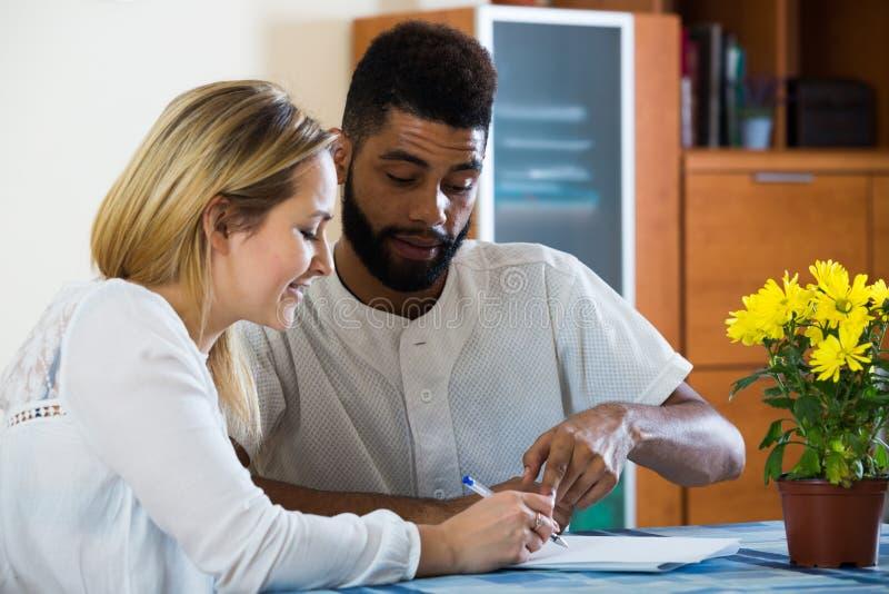 Formes remplissantes de jeunes couples d'application d'opérations bancaires dans domestique dedans images libres de droits