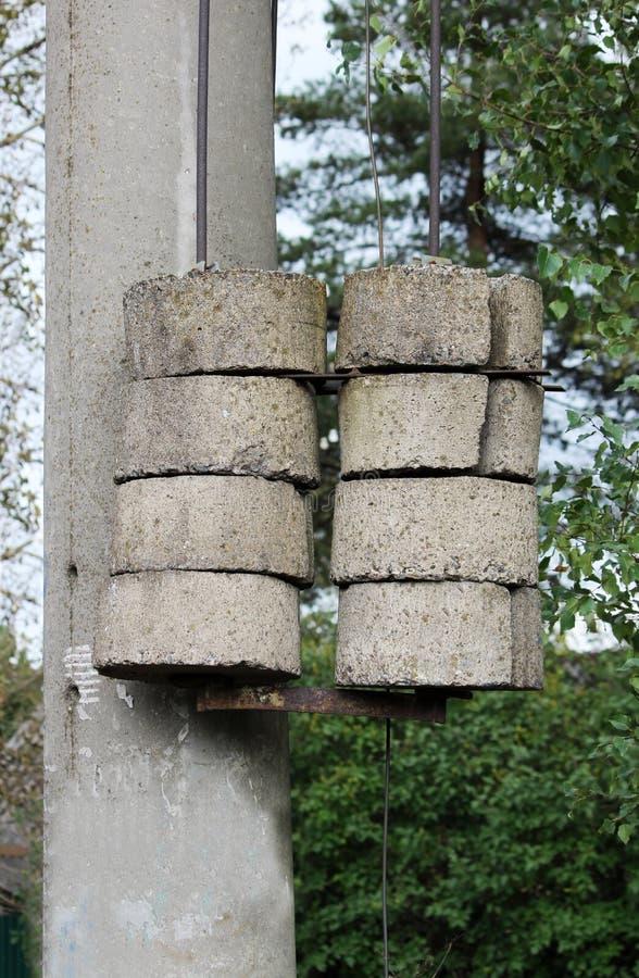 Formez les câbles avec les contrepoids concrets sur un poteau près du chemin de fer photo stock