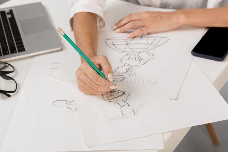 Formgivare för affärskvinna som isoleras över grå väggbakgrund som sitter på tabellteckningen arkivfoton