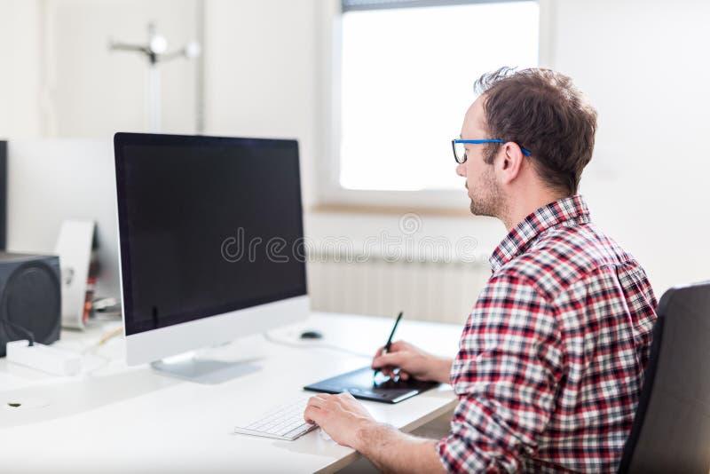 Formgivare för ung man som använder diagramminnestavlan, medan arbeta med datoren royaltyfri fotografi
