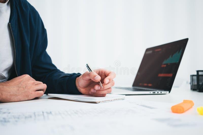 Formgivare för ung man som skissar ett konstruktionsprojekt på anteckningsboken och drar plan, medan arbeta på kontoret royaltyfri bild