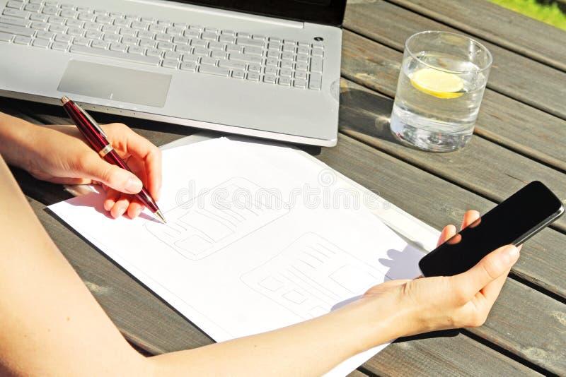 Formgivare som drar en wireframe för mobil rengöringsdukapplikation arkivfoto