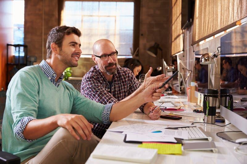 Formgivare som tillsammans arbetar på skrivbord i modernt kontor arkivfoto