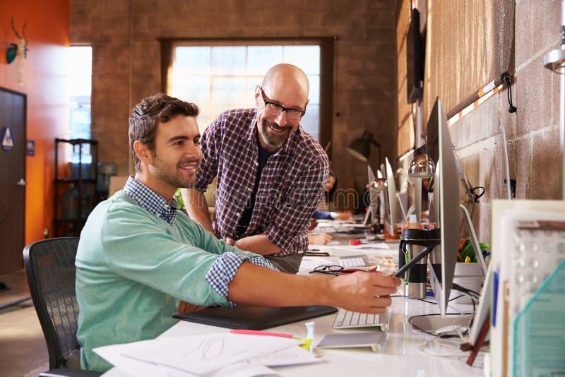 Formgivare som tillsammans arbetar på skrivbord i modernt kontor royaltyfri fotografi