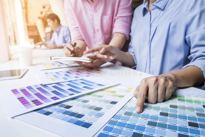 Formgivare som tillsammans arbetar på skrivbord i modernt kontor arkivfoton