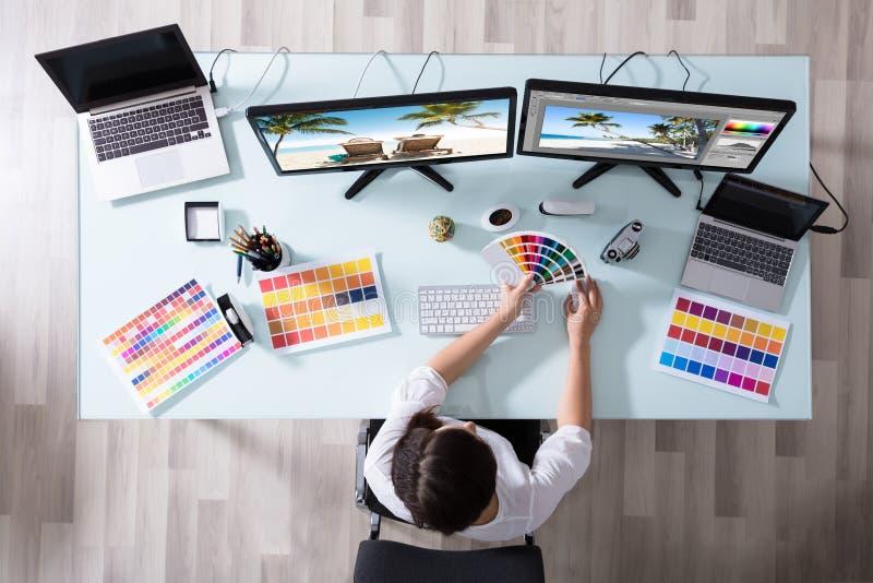 Formgivare Using Color Swatch, medan arbeta på den åtskilliga datoren arkivfoto
