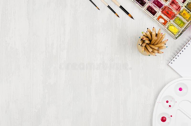 Formgivarearbetsplatsen - brevpapper för kreativitet - vattenfärgen målar, paletten, borstar, färgade blyertspennor på den vita w arkivbilder