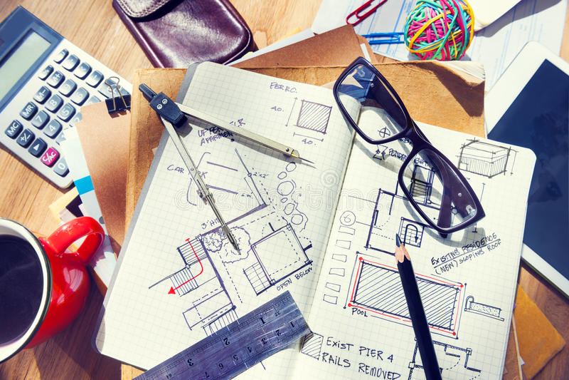 Formgivares skrivbord med arkitektoniska hjälpmedel och ritningen arkivfoto