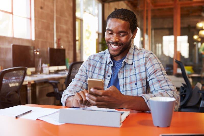 FormgivareSitting At Meeting tabell som smsar på mobiltelefonen royaltyfri bild