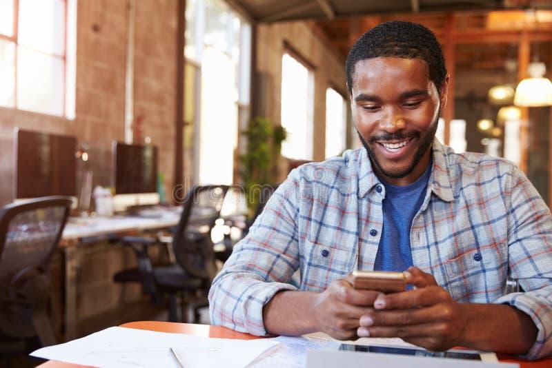 FormgivareSitting At Meeting tabell som smsar på mobiltelefonen arkivfoto