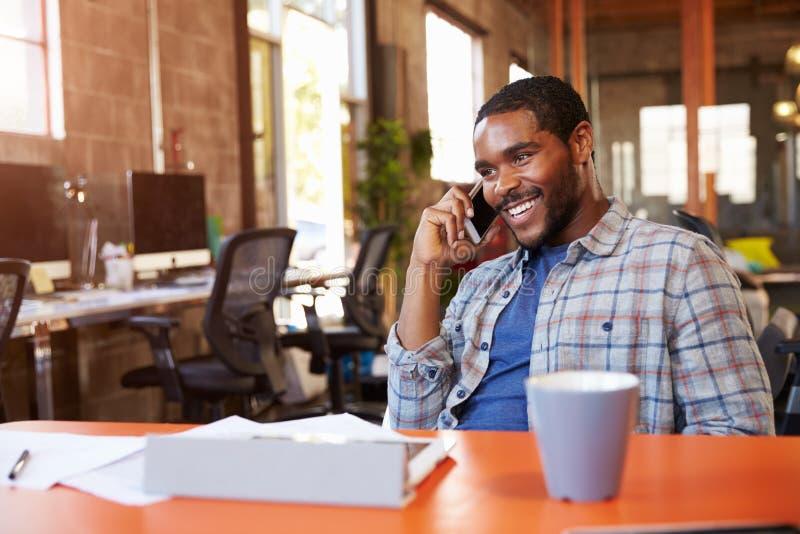 FormgivareSitting At Meeting tabell som talar på mobiltelefonen royaltyfria bilder