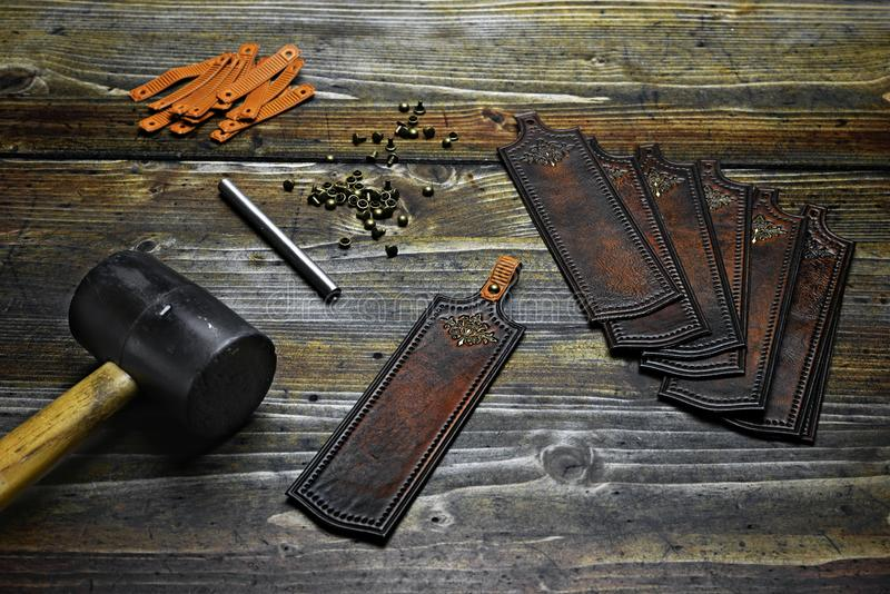 Forming the bookmarks from decorated leather parts with metal rivets, hammer and puncher.  royalty free stock photo