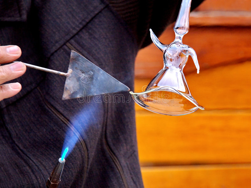 Forming the glass. Glassblower forming a whirling dervish figure from molten glass stock photography
