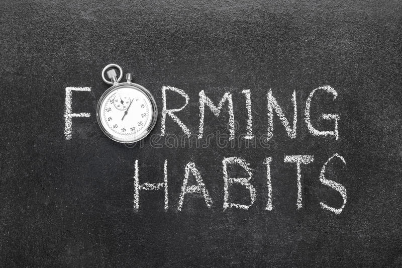 Forming habits watch. Forming habits phrase handwritten on chalkboard with vintage precise stopwatch used instead of O stock images
