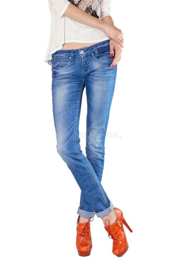 Formschöne weibliche Beine gekleidet in den Blue Jeans lizenzfreie stockbilder