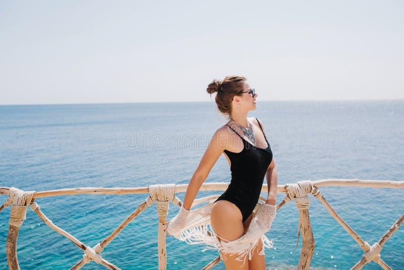 Formschönes würdevolles Mädchen in der modischen schwarzen Badeanzugstellung auf dem Seehintergrund, der den Horizont betrachtet  stockfotos