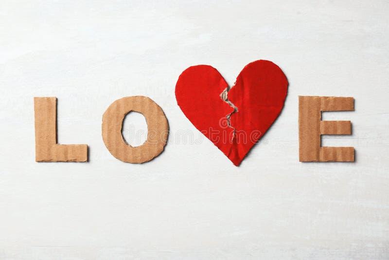 Formułuje «miłości «z poszarpanym kartonowym sercem i listami na lekkim tle, odgórny widok obrazy stock