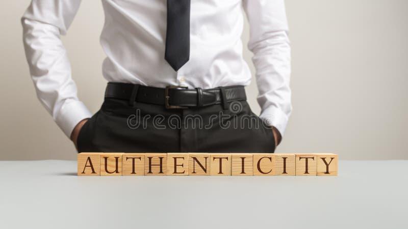 Formułuje autentyczność literującą na biurku z drewnianymi sześcianami zdjęcie royalty free