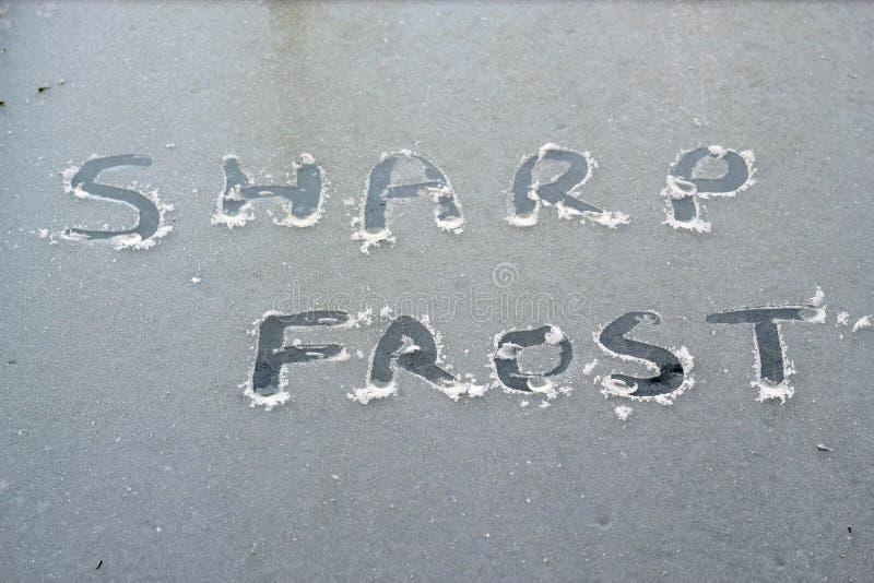 Formułuje ostrze oszroniejącego pisać w lód na okno fotografia stock