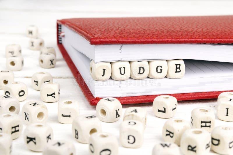 Formułuje sędziego pisać w drewnianych blokach w czerwonym notatniku na bielu zaleca się fotografia royalty free