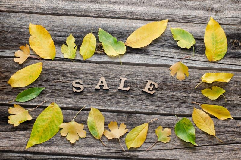 Formułuje sprzedaż na drewnianym tle, rama żółci liście zdjęcia royalty free